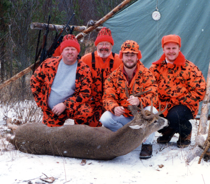 Group photo, 4 men in front of wall tent with Ken's big buck.