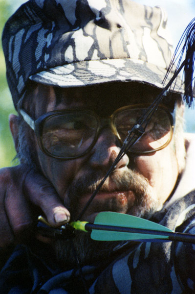 Close-up of Dr Ken Nordberg with bow at full draw.