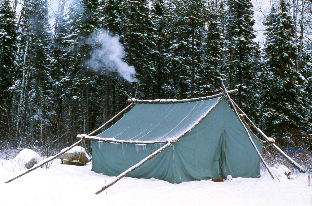 Doc's wall tent in the snow, with white snow coming out of the wood stove's chimney.